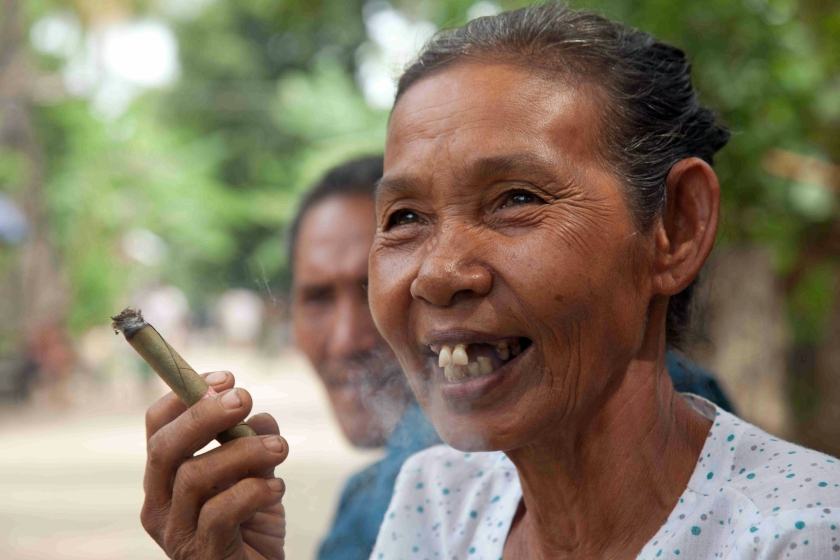 Older Burmese woman smoking cheroot